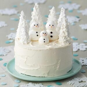 Round, white cake with three meringue snowmen with white trees made from ice cream cones behind them.