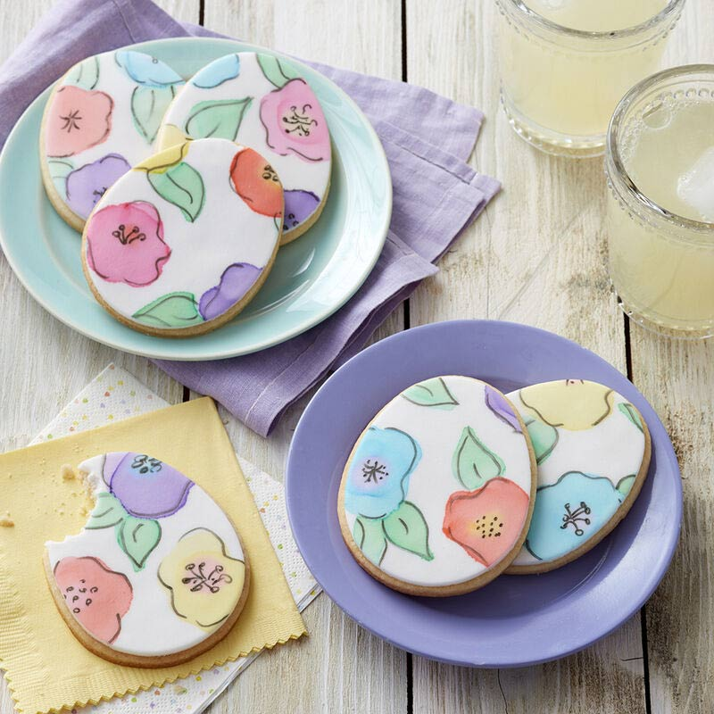 Egg-shaped cookies topped with white fondant painted with flowers