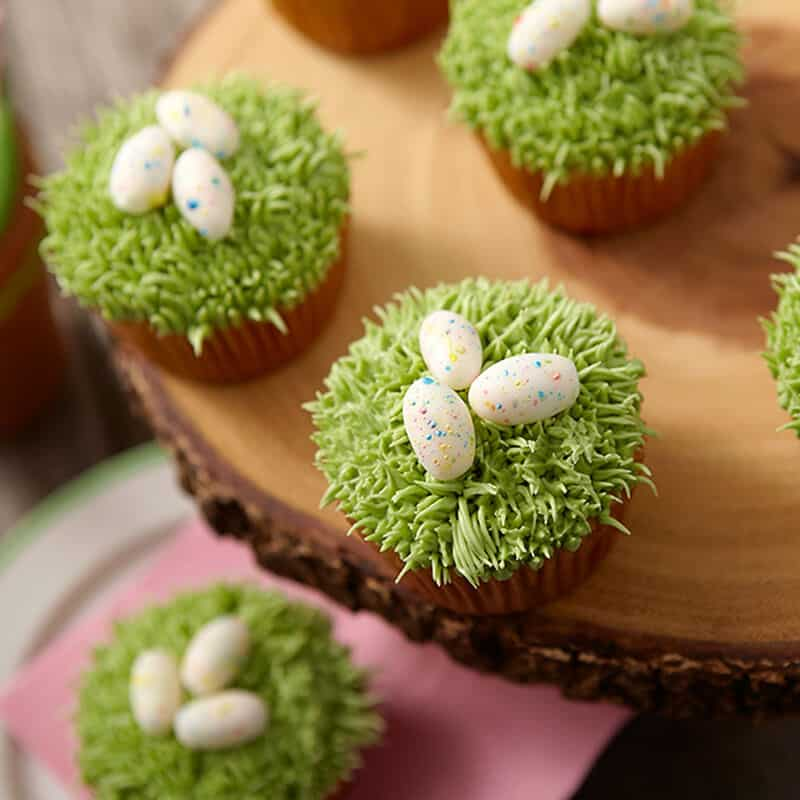 cupcakes topped with pipped green grass and speckled candy Easter eggs