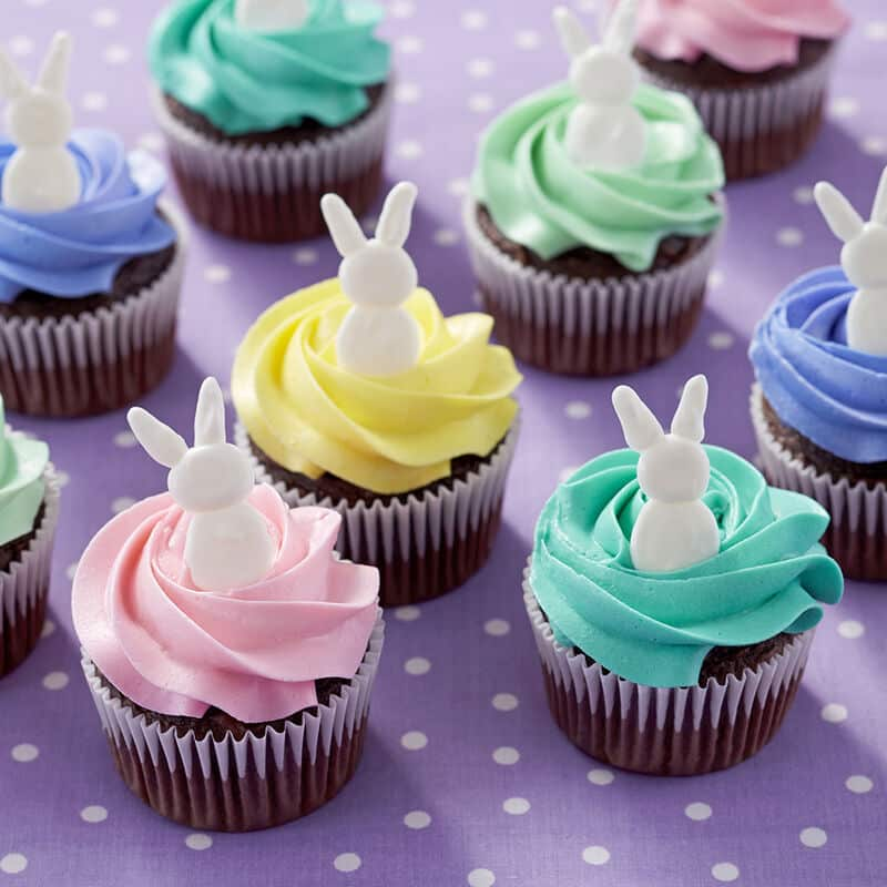 cupcakes topped with a swirl pattern buttercream frosting and topped with an easter bunny decoration