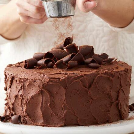 Chocolate cake with chocolate buttercream frosting being sprinkled with chocolate powder