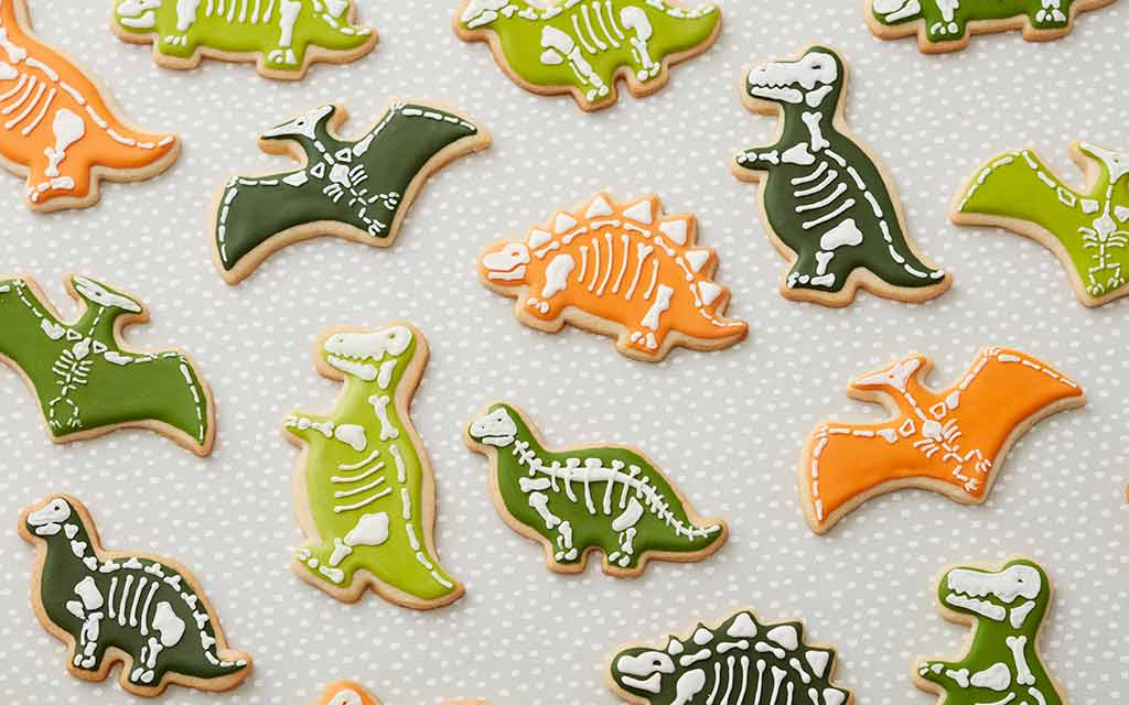 sugar cookies shaped like dinosaurs and decorated with colored green and orange royal icing