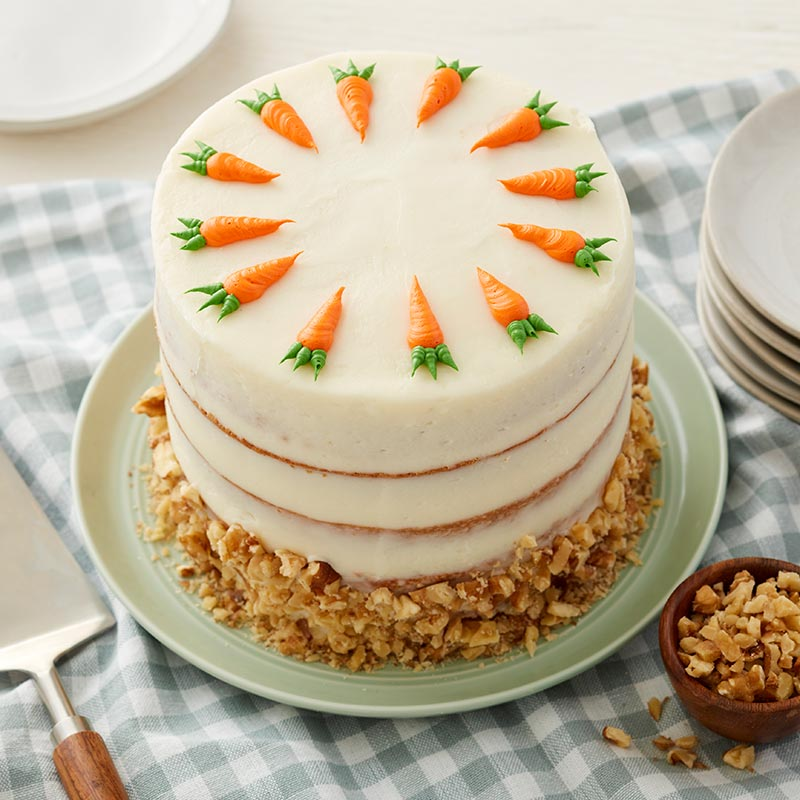 Round carrot cake with cream cheese frosting and walnuts. Topped with buttercream piped carrots